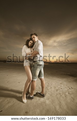 Young sexy couple on beach with sun rising in background .Fashion color - stock photo