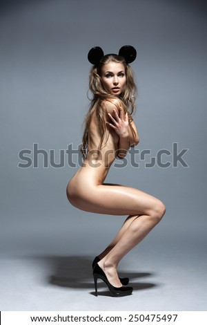 Young sexy european fashion female super model with long hair, legs, perfect skin and awesome body is posing nude, undressed, topless in studio wearing black expensive shoes and minnie mouse ears - stock photo