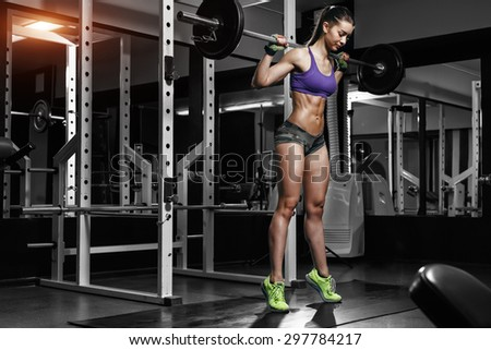 Young sexy girl in the gym doing squat - stock photo