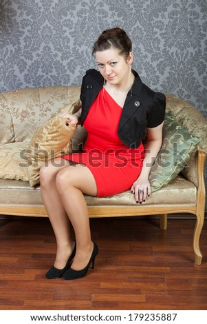 young sexy girl sits on a sofa - stock photo