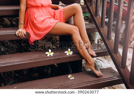 Young sexy girl wear summer peach dress,tropical flowers,long toned legs,cosmetology,sugar waxing,tan skin body,bright toned colors.Young pretty brunette woman,wearing bright clothes,outdoor fashion - stock photo