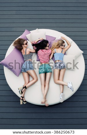 young sexy girls lying on big round bed, view from above; females with beautiful body lying on pillows; - stock photo