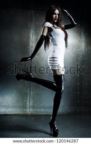 Young sexy goth woman on wall background. - stock photo