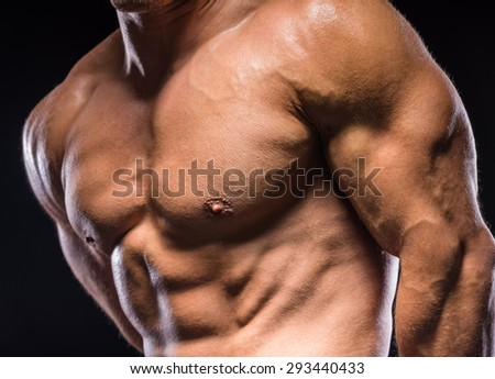 Young sexy handsome athletic man with naked torso on dark background. - stock photo