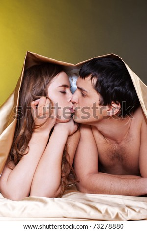 Young sexy heterosexual couple making love in bed - stock photo