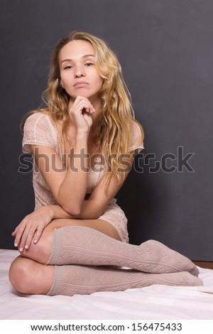Young sexy lady in lingerie and socks over old vintage background - stock photo
