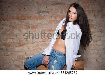 Young sexy lady wearing black bra, white shirt and blue jeans - stock photo
