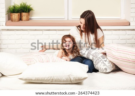 young sexy mother spending daytime, having fun with her daughter, lying on the bad with pillows in light room - stock photo