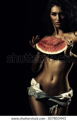 Young sexy naked brunette girl in jeans shorts with beautiful slim tan body holding big juicy red water melon slice standing on black background copyspace, vertical picture - stock photo