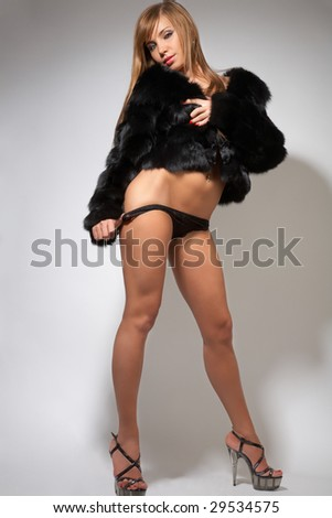 young sexy nude girl in black fur coat, lingerie and high-heeled shoes on gray - stock photo