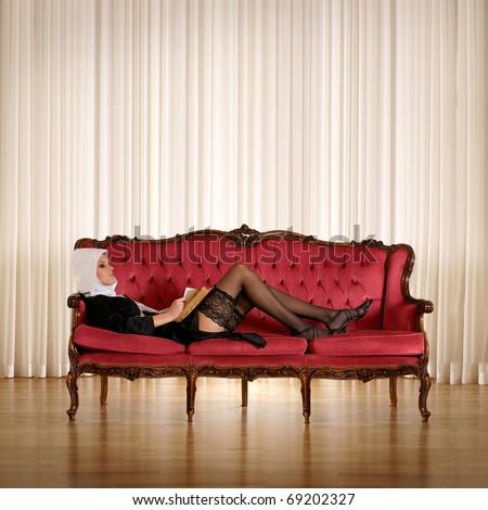 Young sexy nun over red sofa - stock photo