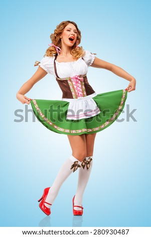 Young sexy Oktoberfest woman wearing a traditional Bavarian dress dirndl dancing and singing on blue background. - stock photo