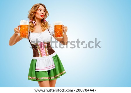 Young sexy Oktoberfest woman wearing a traditional Bavarian dress dirndl serving two beer mugs on blue background. - stock photo