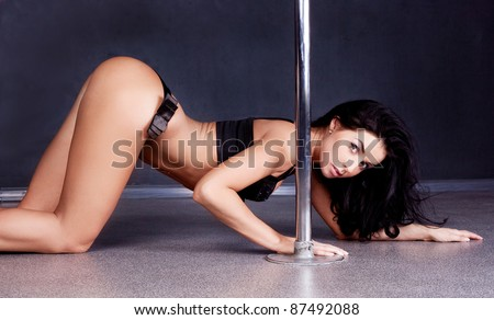 Young sexy pole dance woman against dark background - stock photo