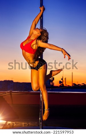 Young sexy pole dance woman on urban background. - stock photo