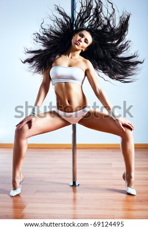 Young sexy pole dance woman shaking hair. - stock photo