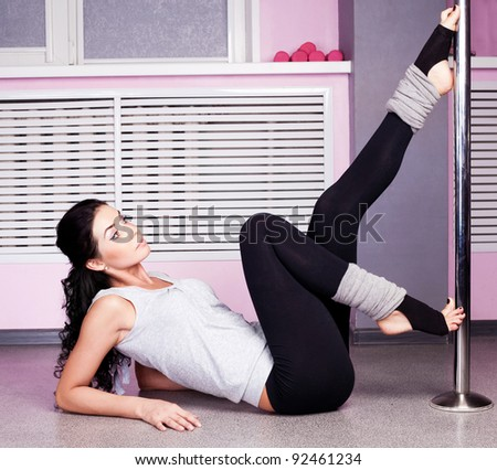 Young sexy pole dance woman, wearing sports clothes - stock photo