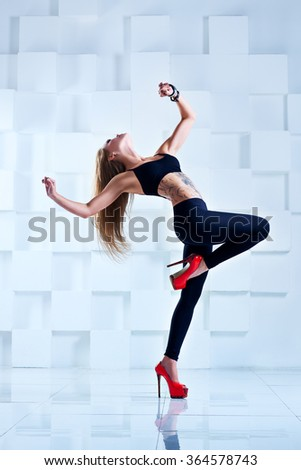 Young sexy slim woman dancer in black clothing in bright white interior. Tattoo on body. - stock photo