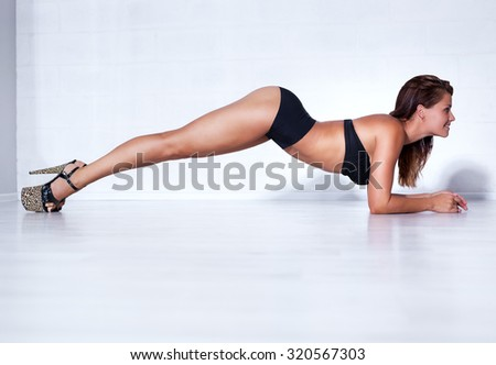 Young sexy slim woman dancer in lingerie stretching on white wall background. - stock photo