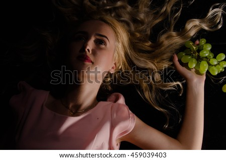 Young sexy smiling beautiful woman holding a bunch of grape in her hands with long hair  - stock photo