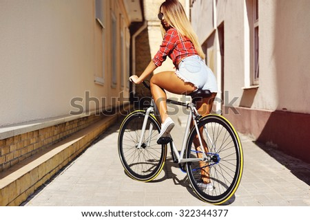 Young sexy woman back on sport fixed gear bicycle posing on outdoor  - stock photo