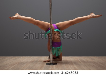 Young sexy woman exercise pole dance before a gray background - stock photo