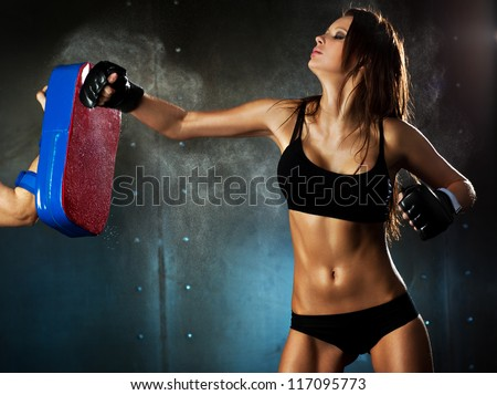 Young sexy woman hitting punching bag. - stock photo