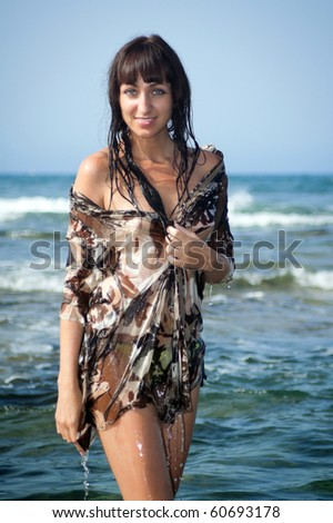 Young sexy woman in a wet beach dress with bare shoulders standing in ocean water. Tenerife, Spain. - stock photo