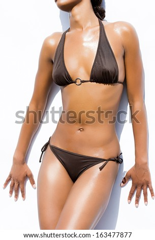 Young sexy woman in black bikini over white background - stock photo