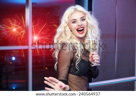 Young sexy woman in black elegant dress holding wineglass with champagne  - stock photo
