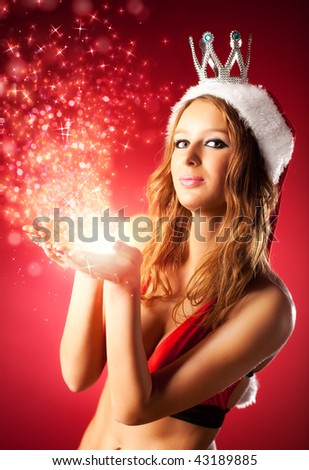 Young sexy woman in santa clothing with magic sparks. - stock photo