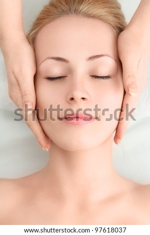 Young sexy woman in spa gets a facial massage - stock photo