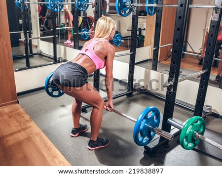 Young sexy woman in the gym doing squat with barbell - stock photo