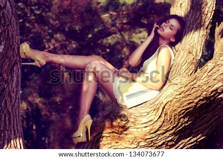 young sexy woman in yellow dress sitting on a tree branch. summer fashion portrait - stock photo
