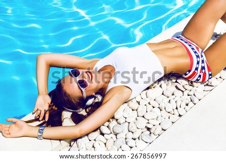 Young sexy woman laying and relaxed near pool at summer holiday nice hot day, wearing sexy mini shorts and crop top, listening and enjoy her favorite music at big headphones. - stock photo