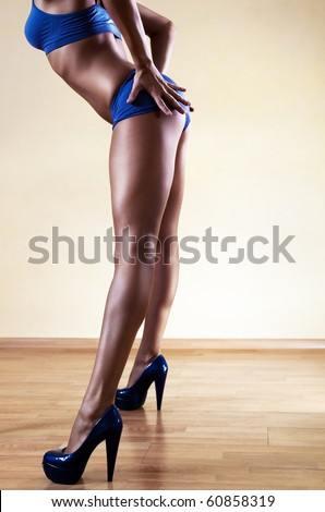 Young sexy woman legs. On wall background. - stock photo