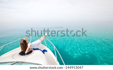 Young sexy woman lies in white dress enjoying on yacht at the sea - stock photo