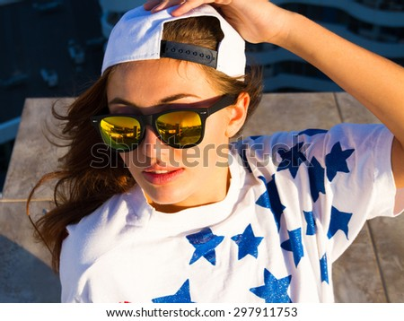 Young sexy woman posing in the roof, wearing american flag print t-shirt, swag white hat mirrored sunglasses and natural make up, enjoying sunset and dreaming. Lifestyle portrait bright toned colors. - stock photo