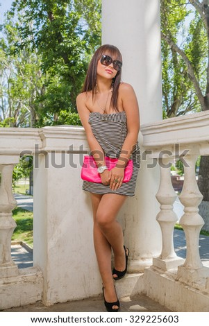Young sexy woman posing leaning back column in trendy sunglasses with fashionable handbag in her hands - stock photo