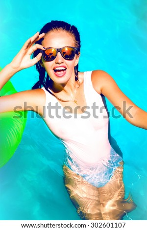 Young sexy woman relaxed at pool at summer nice hot day,wearing sexy full bikini,mirrored sunglasses,and laughing.Look at camera,sunbathing and playing with friends on the pool.Toned,lifestyle closeup - stock photo