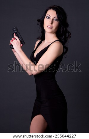 young sexy woman secret agent posing with gun over grey background - stock photo