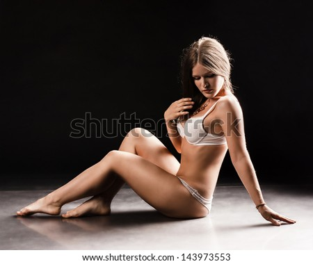 Young sexy woman sit on the floor. studio photo. - stock photo
