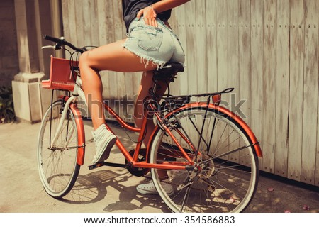 Young sexy woman,wear denim summer outfit and holding mirrored sunglasses,perfect glowing tan skin,attractive and,joy and happiness,trim,athletic figure,perfect female body, and drift show - stock photo