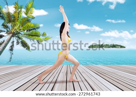 Young sexy woman wearing swimsuit, meditating at the pier of the island resort - stock photo
