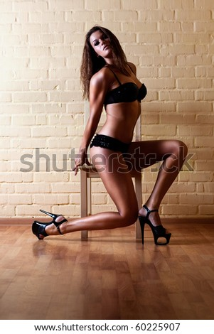 Young sexy woman with chair. - stock photo