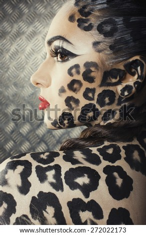 young sexy woman with leopard make up all over body, cat bodyart closeup - stock photo
