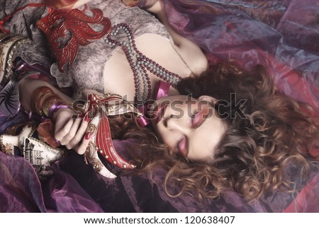 Young sexy woman with venetian masks lay on organza - stock photo