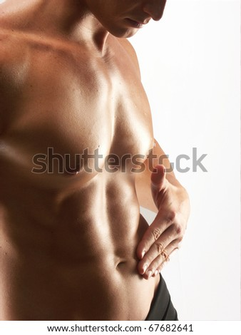 Young shaped man touching his abdomen on white background. - stock photo