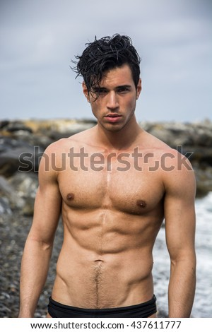 Young shirtless athletic man standing in water by ocean shore - stock photo