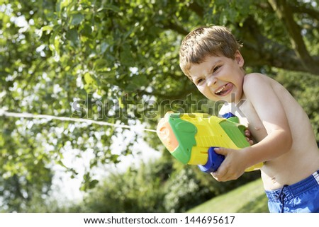 Young shirtless boy with water pistol in the park - stock photo